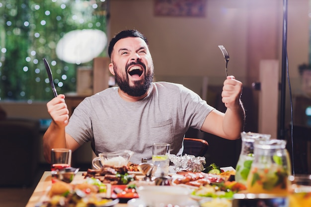 Man at the big table with food. Premium Photo
