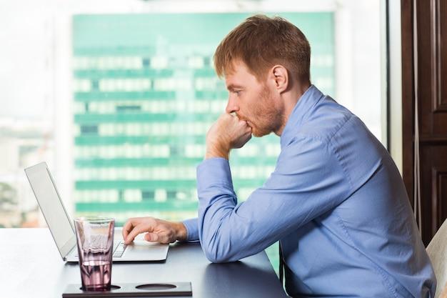 Man biting his nails while looking at a laptop Free Photo