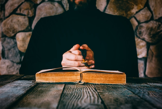 A man in black clothes with a prayer beads in hand praying in front of an old open book. Premium Photo