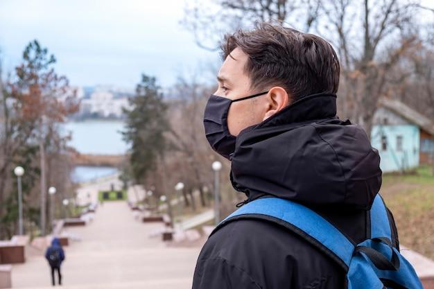 Un uomo in maschera medica nera e una giacca invernale con zaino blu, parco sullo sfondo a chisinau, in moldova Foto Gratuite