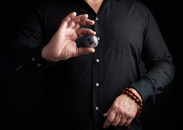 Man in a black shirt holds a stone ball for religious rituals Premium Photo