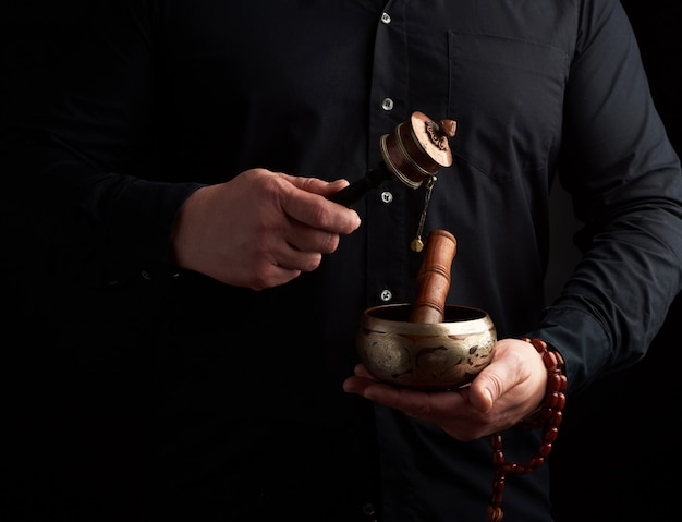 Man in a black shirt holds a tibetan brass singing bowl and a wooden stick Premium Photo