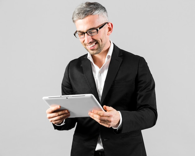 Man in black suit looking at the digital tablet Free Photo