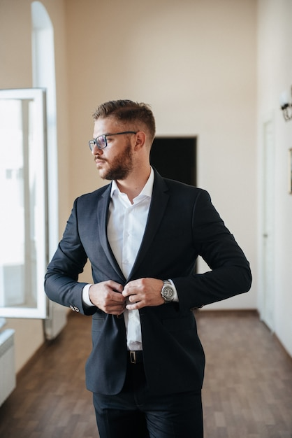 Premium Photo A Man In A Black Suit And White Shirt Poses Indoors For Advertising Men S Clothing Shooting For Men S Clothing Store