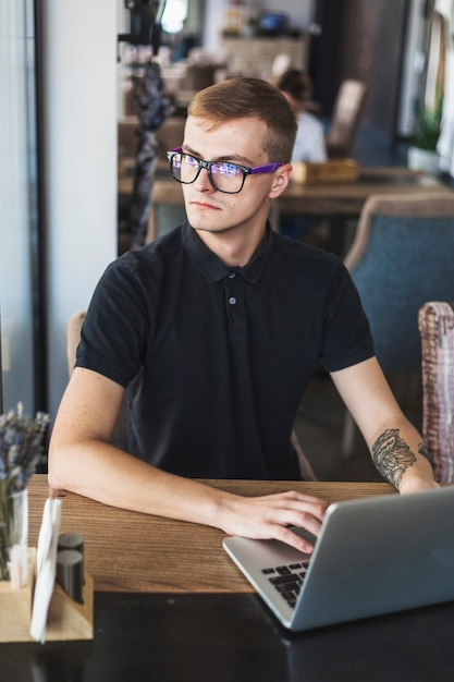 Man in black working on laptop in cafe Free Photo