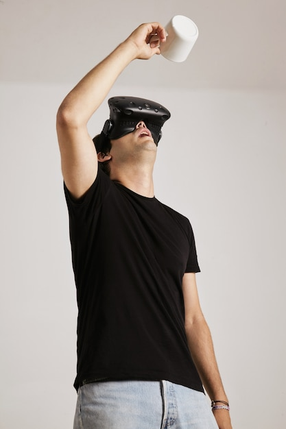 A man in blank black t-shirt and vr headset is looking up into an empty white mug he holds above his head, isolated on white Free Photo