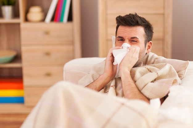 Man blowing his nose while lying sick in bed Free Photo