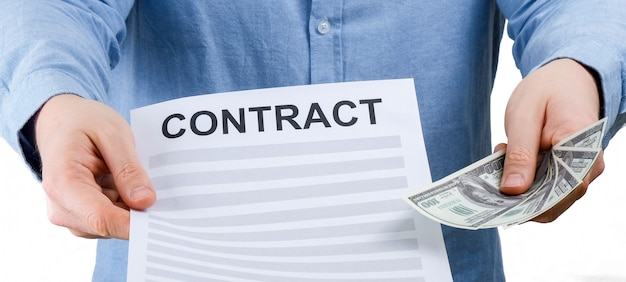 A man in a blue shirt holds a sheet with a contract and us dollars on a white background. Premium Photo