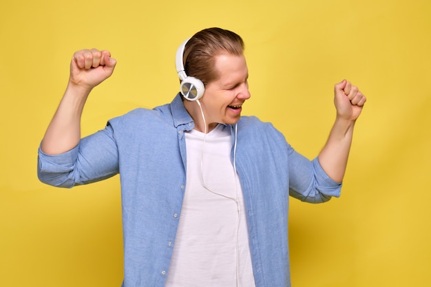 A man in a blue shirt on a yellow background dressed in white headphones and enjoys dancing music. Premium Photo