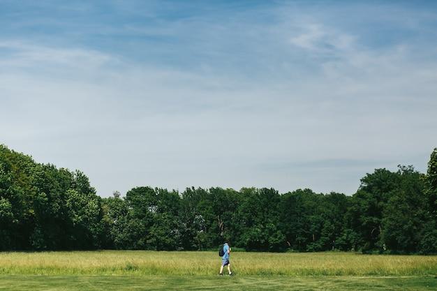 Man in blue shorts walk along the green lawn Free Photo
