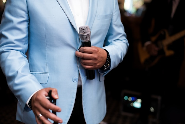 Man in blue suit holds a microphone Free Photo