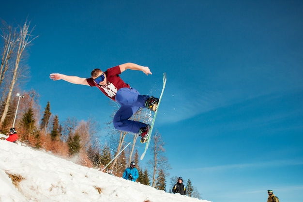 Man boarder jumping on his snowboard against the backdrop of mountains Free Photo