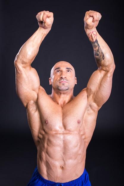Man bodybuilder is demonstrating his perfect muscular. Premium Photo