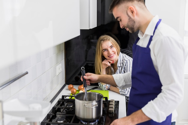 Man boiling water in pot on stove Free Photo