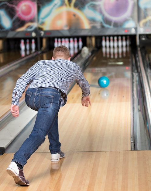 A man in bowling throws the ball in the pins. Premium Photo
