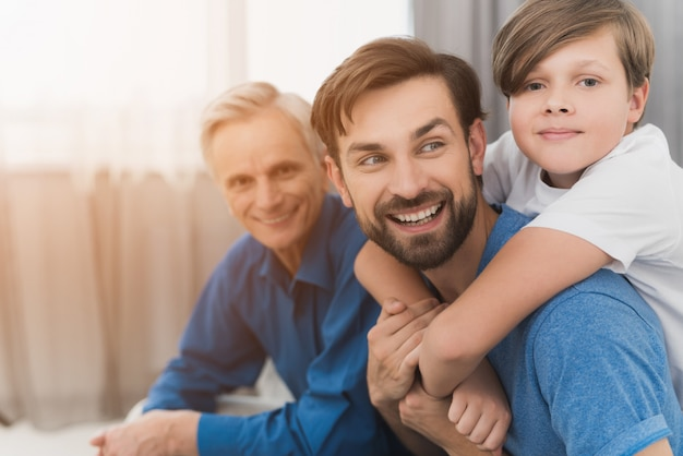 Man, a boy and an old man are posing sitting on a gray sofa Premium Photo
