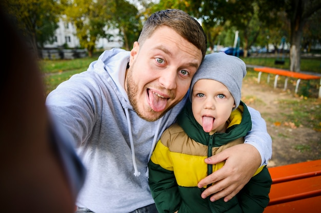 Man and boy taking a selfie with tongues out Free Photo