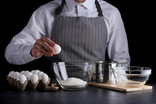 Человек, разбивающий яйцо в миске, готовит печенье Premium Фотографии