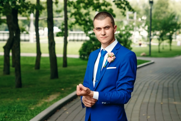 The man, the bridegroom in a classic blue suit against a background of green nature. wedding, groom, family creation. Premium Photo
