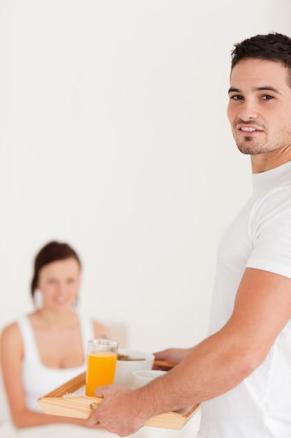カメラを見て朝食を持っている男 Premium写真