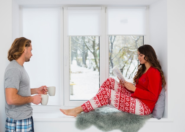 Man bringing coffee mug to the woman sitting on window sill reading book Free Photo