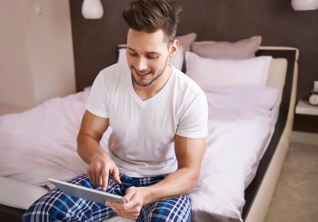 寝室でインターネットページを閲覧している男性 無料写真