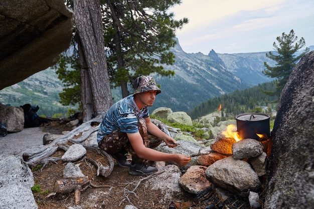 Man built a campfire in woods in nature. survive Premium Photo