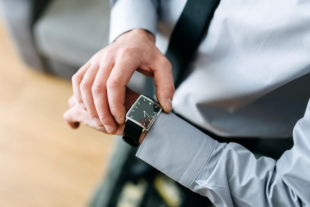 A man in a business suit checking a wrist watch on his hand Premium Photo