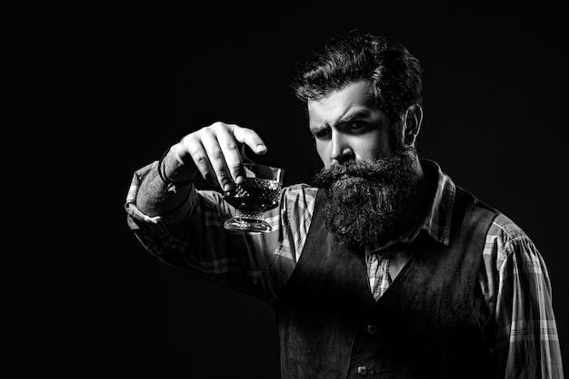 Man or businessman drinks whiskey on black background. bearded and glass of whiskey. Premium Photo