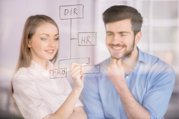 Man and businesswoman drawing on glass screen in office. Premium Photo