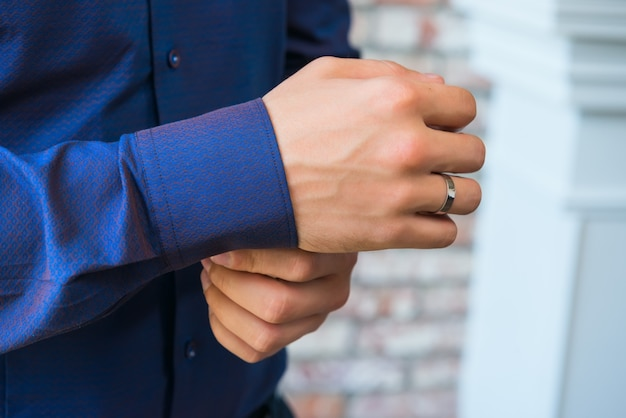 Man buttoning on the sleeve of his blue-violet shirt Premium Photo