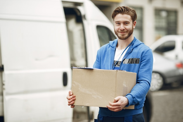 Man by the truck. guy in a delivery uniform. Free Photo