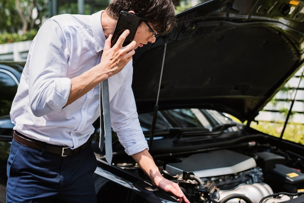 Man calling for help to fix his car Free Photo