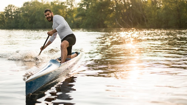 Man in canoe rowing concept Free Photo