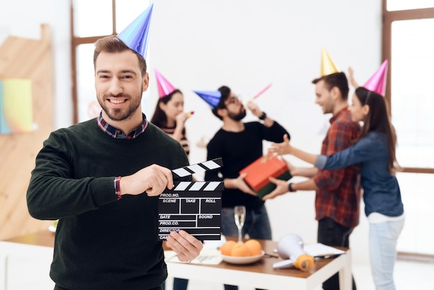 The man in the cap keeps the movie clapperboard. Premium Photo