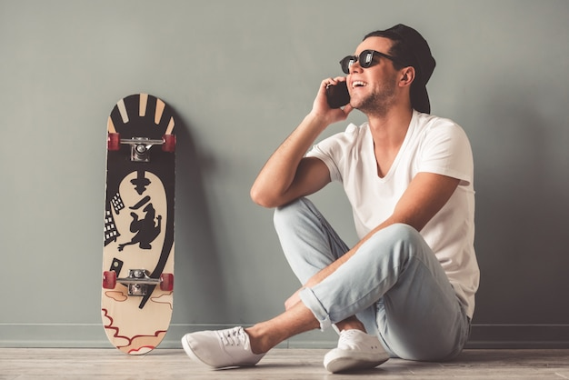 Man in cap and sunglasses is talking on the mobile phone Premium Photo