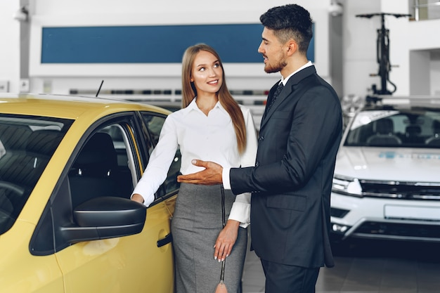 Мужчина-автодилер показывает покупательнице новую машину Premium Фотографии