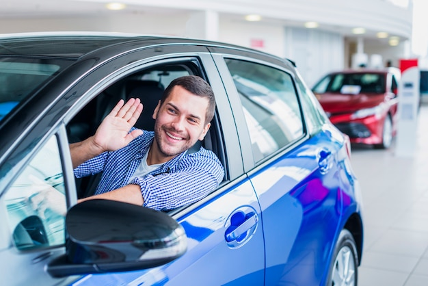 Man in car at dealership Free Photo