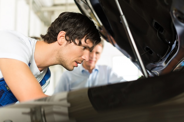 Man and car mechanic looking beneath a hood Premium Photo