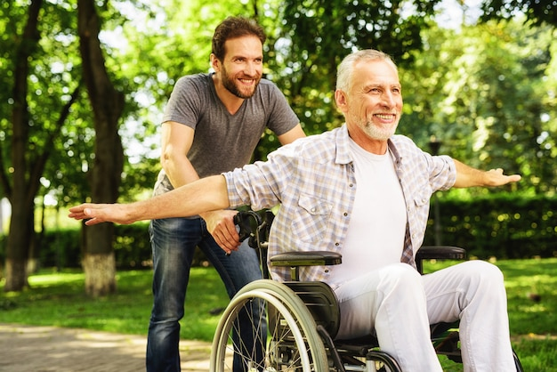 Man carry father on wheelchair. laughing men. Premium Photo