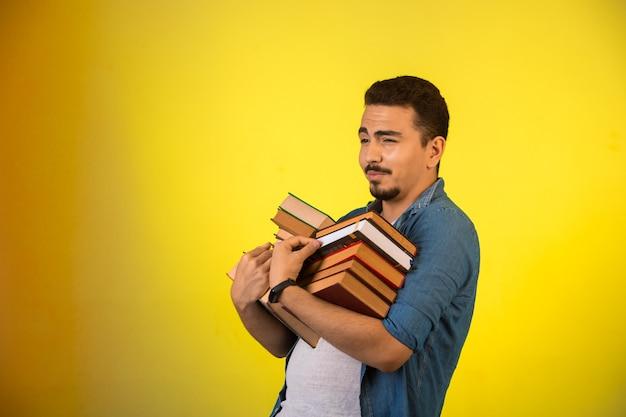 Человек, несущий стопку тяжелых книг двумя руками и улыбаясь. Бесплатные Фотографии