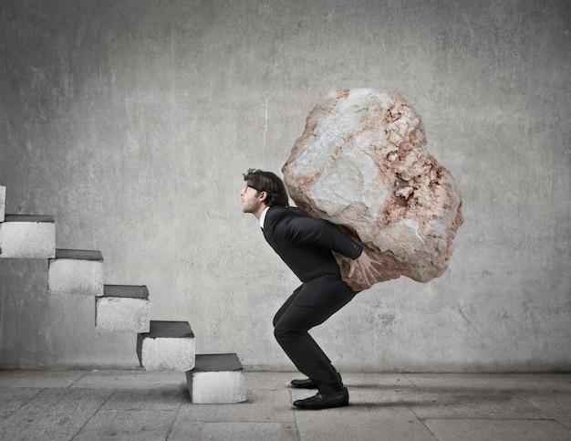 Man carrying a big stone Premium Photo