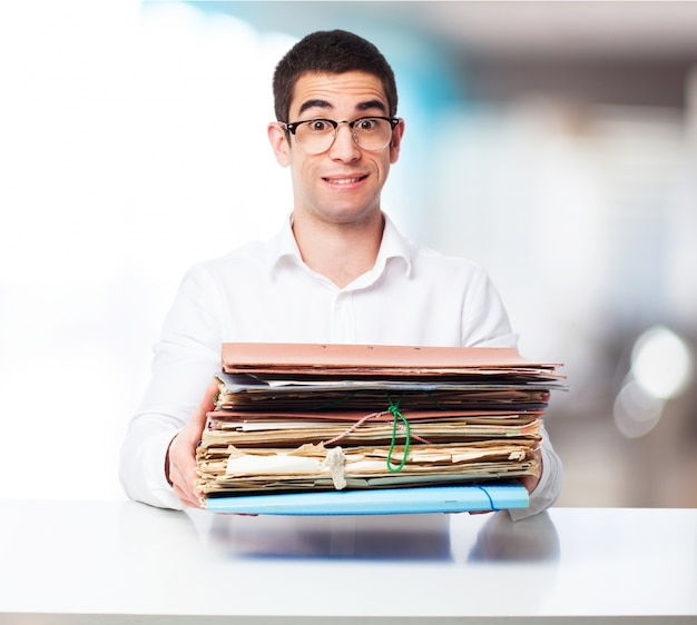 Man carrying a bunch of folders in an office Free Photo