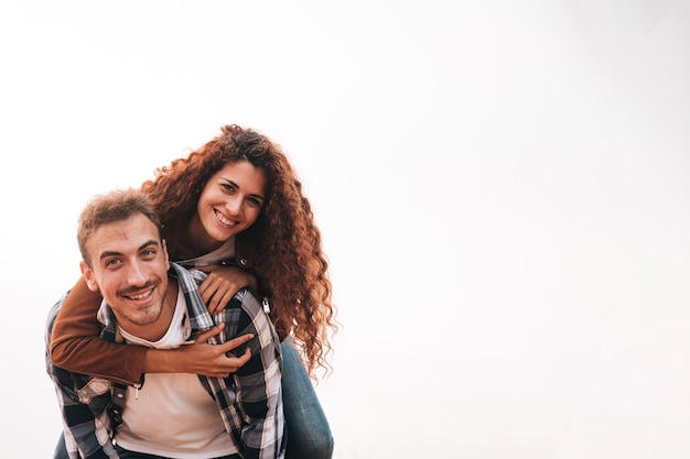 Man carrying girlfriend on his back Free Photo