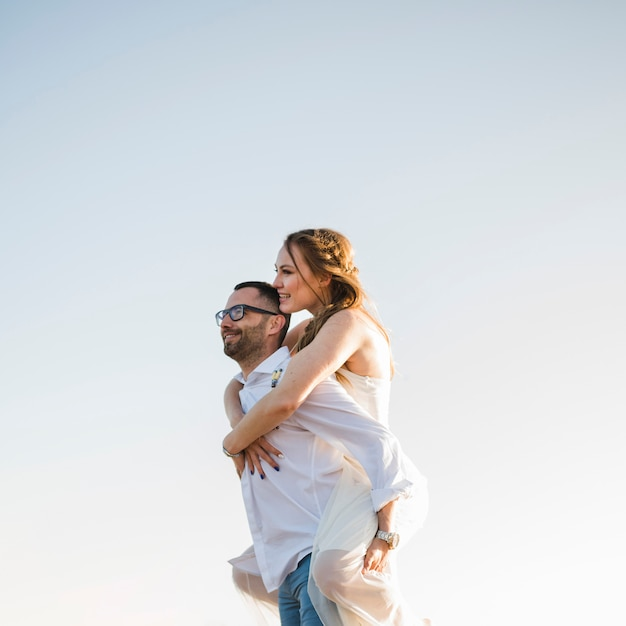 Man carrying his girlfriend on his back at a beach against blue sky Free Photo