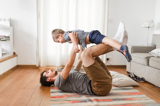 Человек, несущий сына на ноге во время тренировки Бесплатные Фотографии