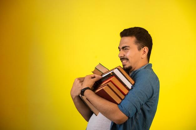 Uomo che porta una pila di libri pesanti. Foto Gratuite