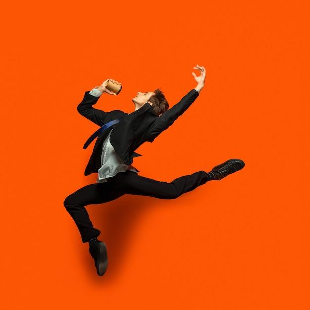 Uomo in abiti casual stile ufficio saltando isolato sulla parete Foto Gratuite