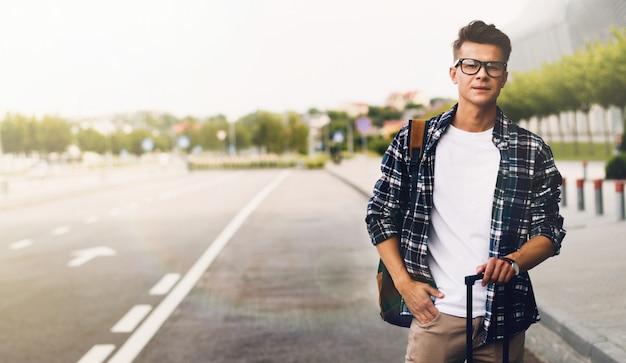 Человек ловит такси в аэропорту с чемоданом Premium Фотографии