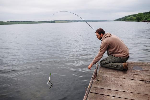 Man Catching Fish With Fishing Rod In Lake Photo Free Download